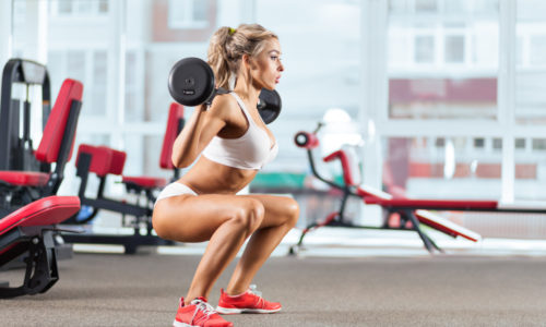 Sportive woman doing squatting with a barbell in the gym